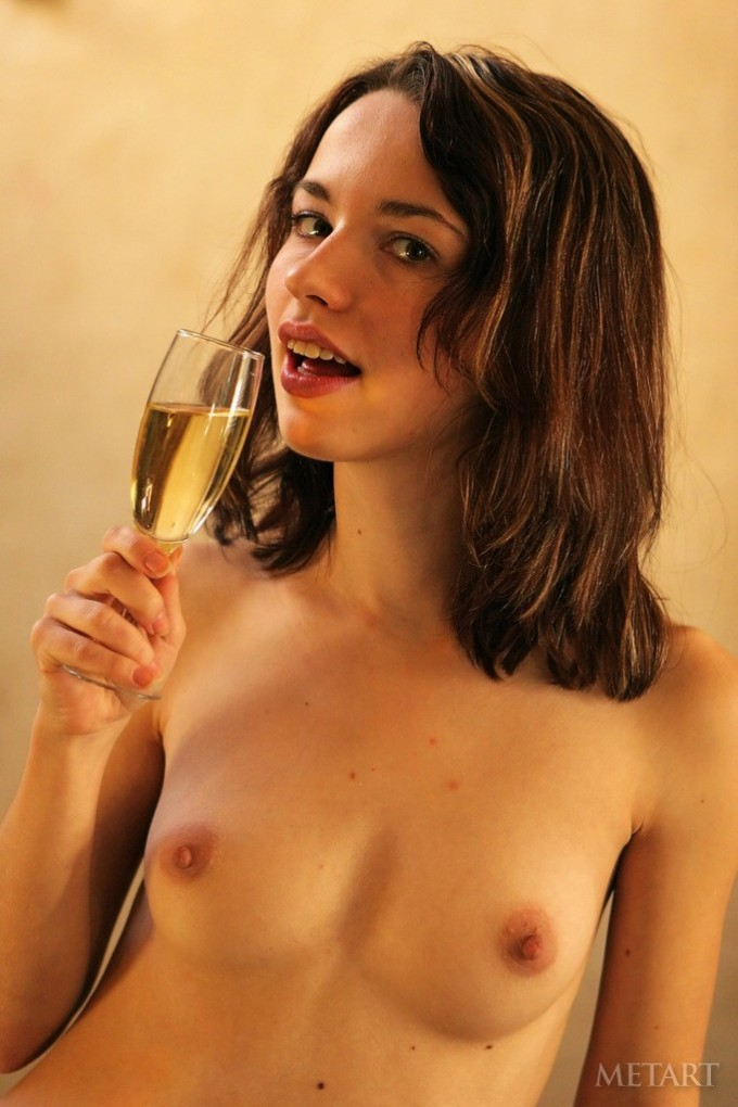 Artistic babe is posing with a glass of wine
