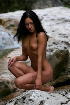 Slender brunette posing on the rocks