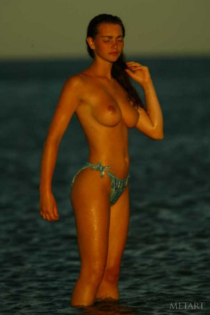 Busty brunette posing during a sunset