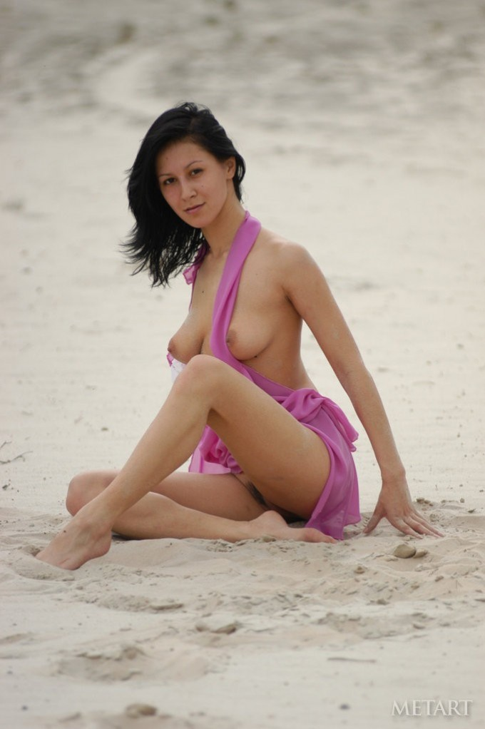 Dark-haired babe posing on the beach