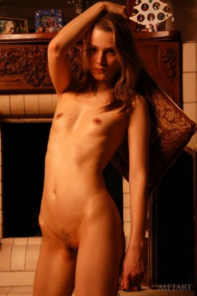 Sweet model posing at the fireplace