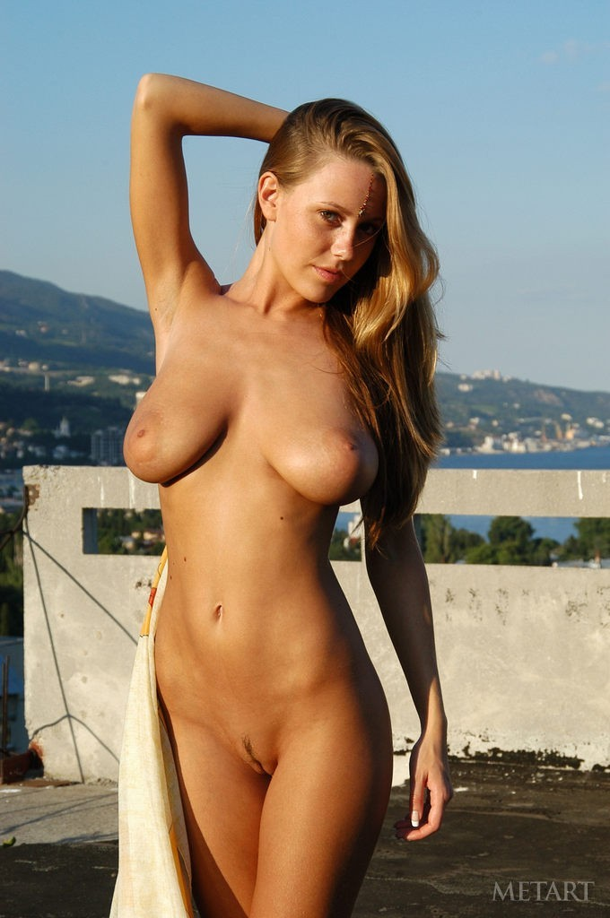 Busty brunette is posing outdoor