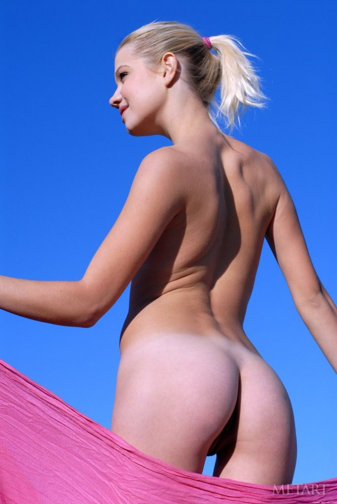 Blonde is on a beach with a pink towel