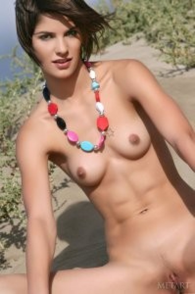 Gorgeous girl gets sand on her flawless body
