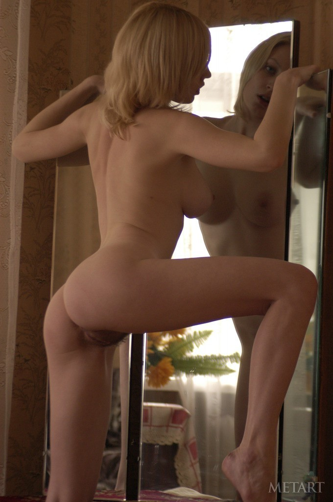 Curvy blonde is in front of a mirror