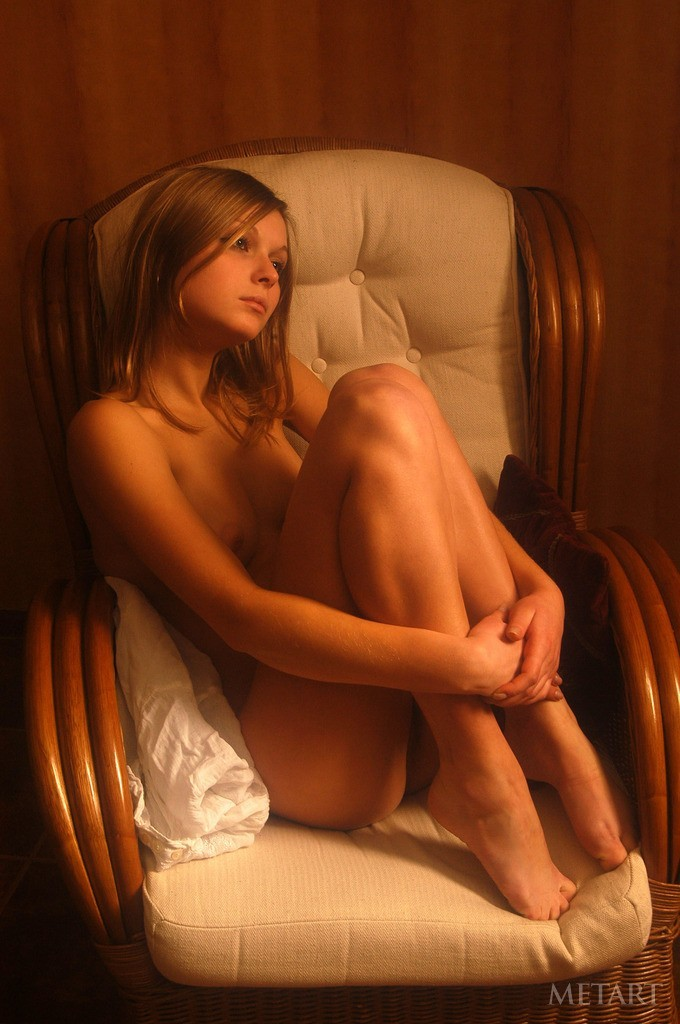 Brunette gets naked on an armchair