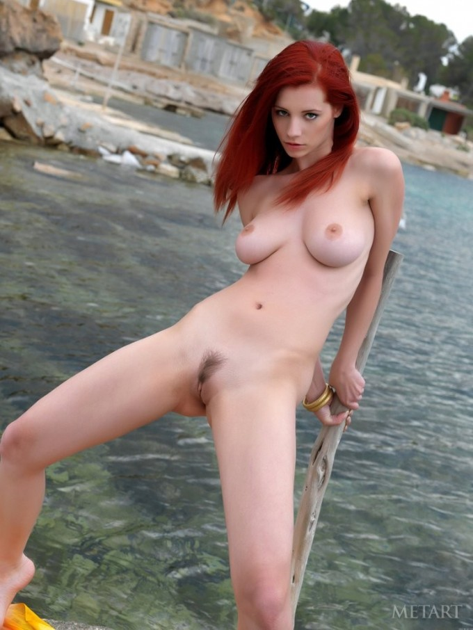 Redhead babe poses near a body of water