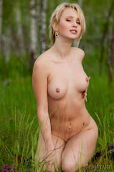 Blonde with a hairy pussy is naked in the forest