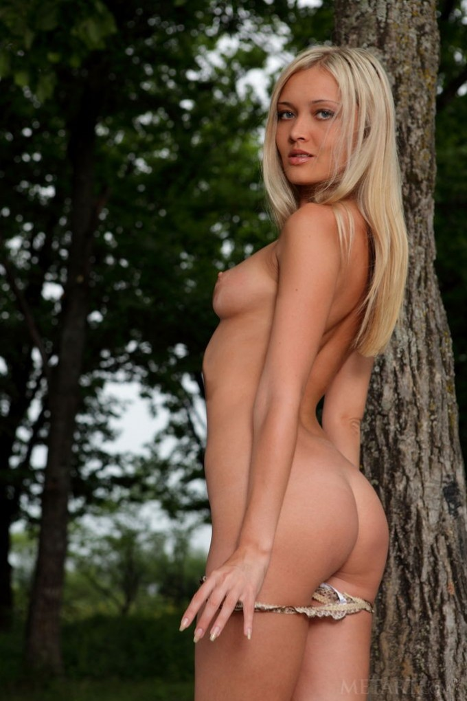 Blonde is leaning against a tree and sitting on a bench