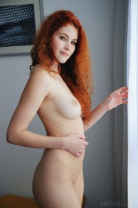 Ginger babe explores her sweet pussy in armchair