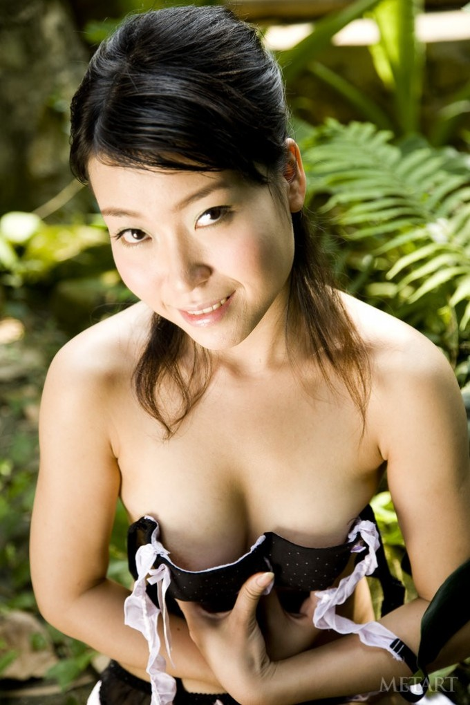 A kinky Asian chick is doing poses in the garden