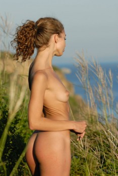 Thin, fit girl having naked fun in a field