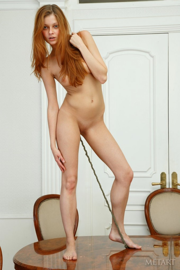 Redhead is posing on the table