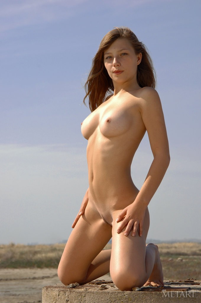 Busty girl poses on an empty field